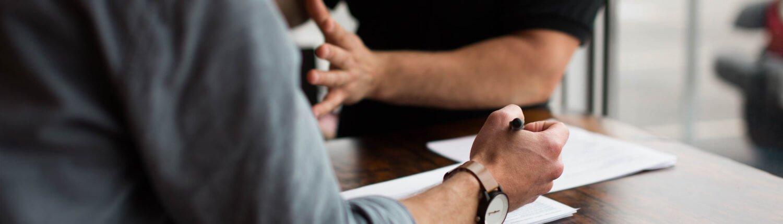 Zwei Männer sitzen an einem Tisch und diskutieren ein Thema