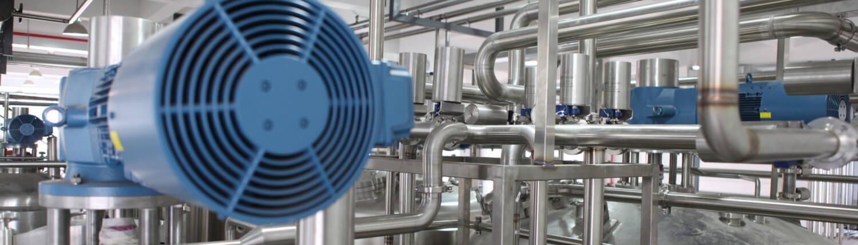 Industriehalle mit Rohrleitungen, die zu einem Kessel führen